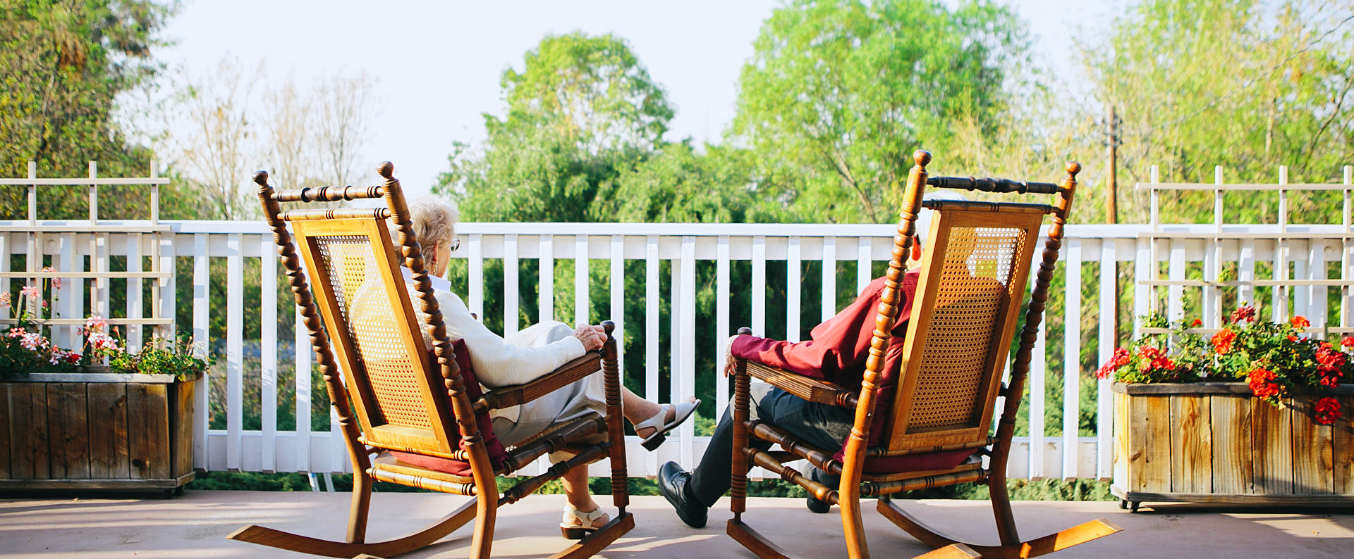 a porch with two seniors on a rocking chair