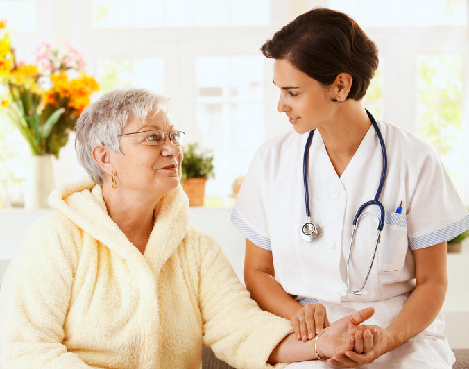 a nurse and a senior woman looking at each other