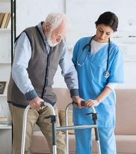 a nurse assisting a senior man use a walker