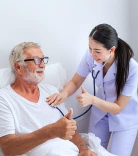 a nurse checking the heartbeat of a senior man